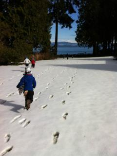 Children running across a snowy lawn towards a view of the ocean